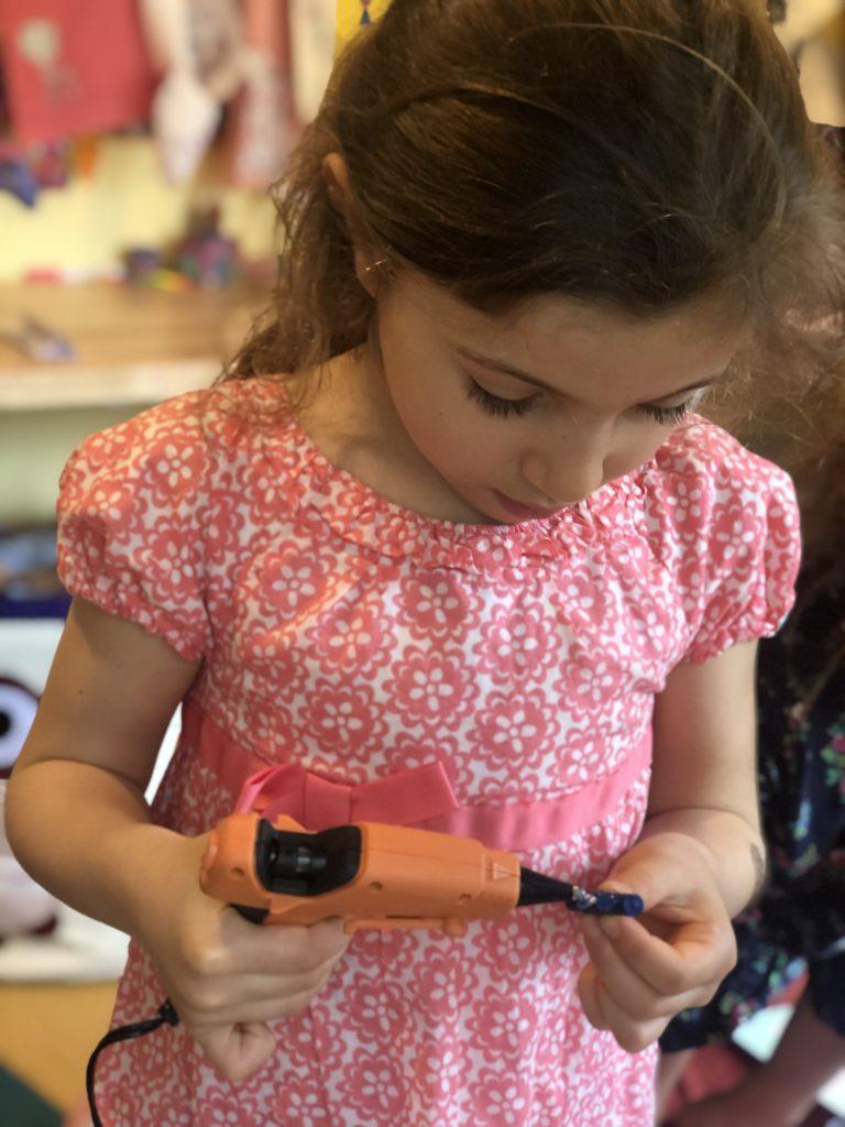 Lydia applies glue to a crayon