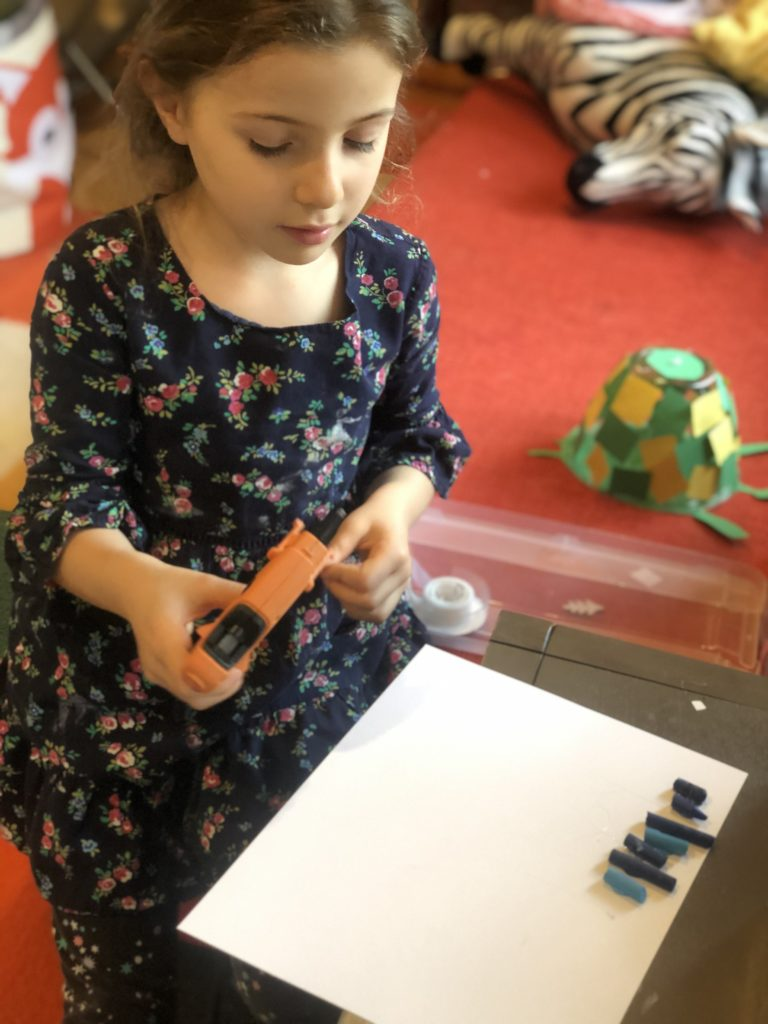 Zoe attaches crayons to the card stock