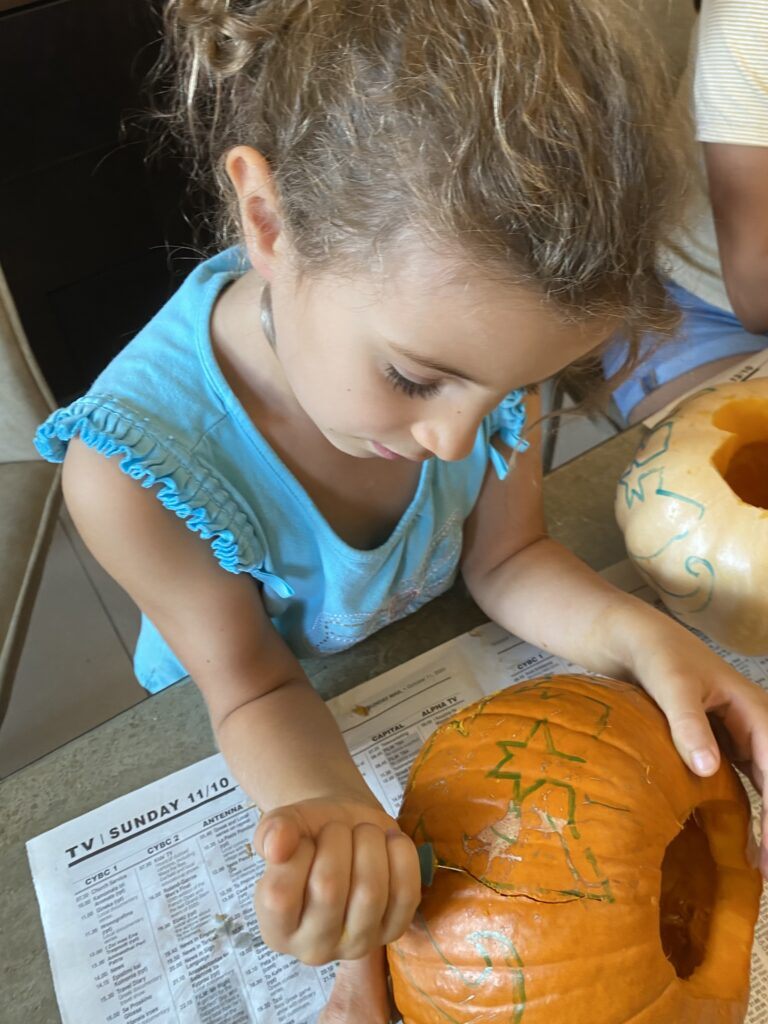 Using pumpkin carving tools to cut out our Merkitty designs.