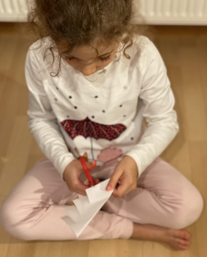 Lydia Panay cutting slits into a folded square piece of paper.
