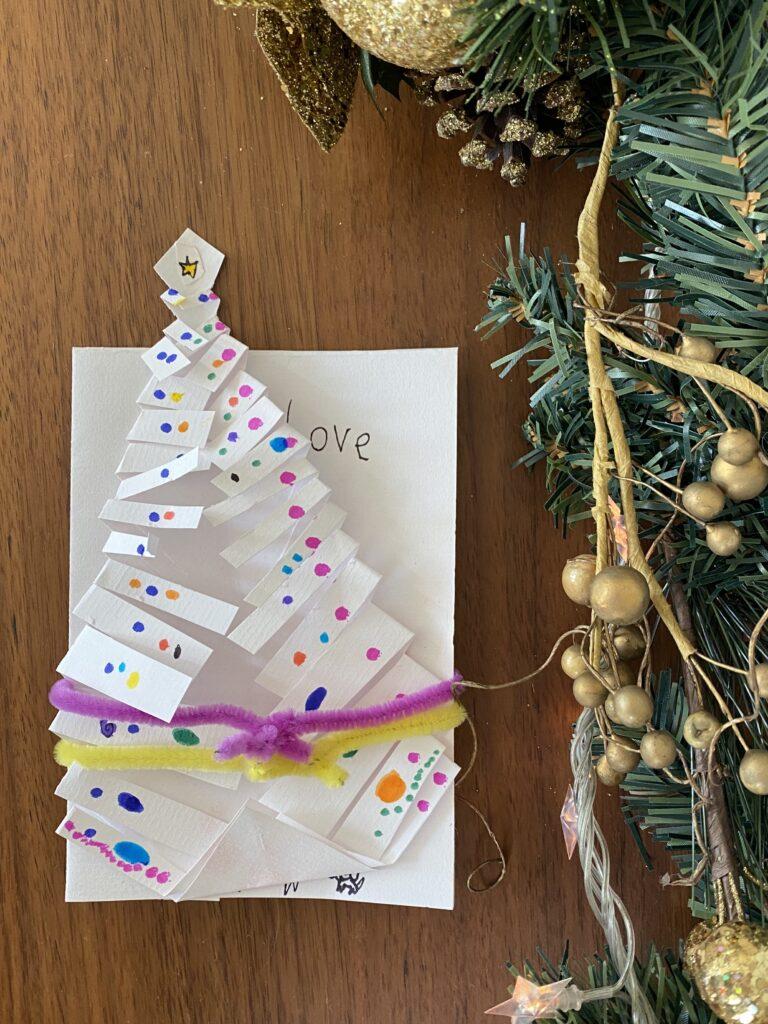 Handmade Christmas tree craft attached to a a handmade card with colorful pipe cleaners.