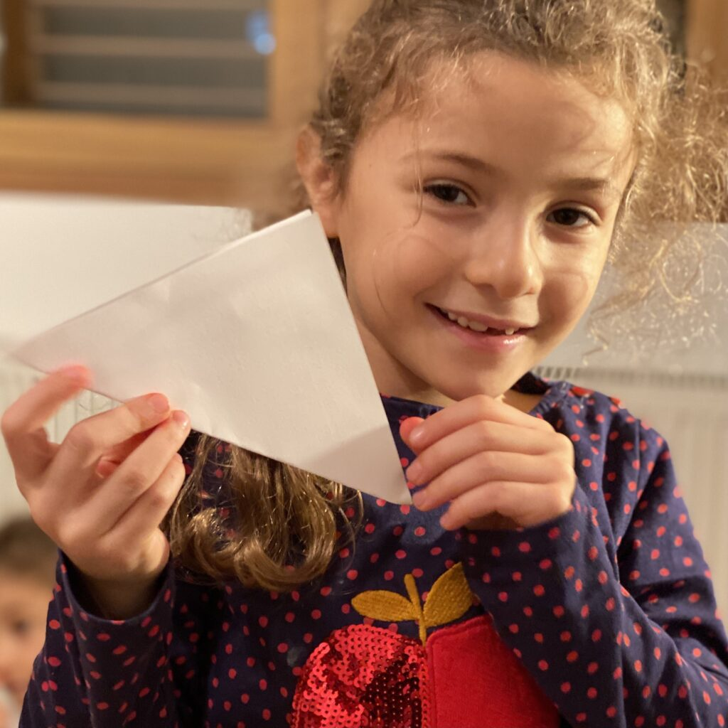 Zoe Panay holding up a folded square piece of paper.